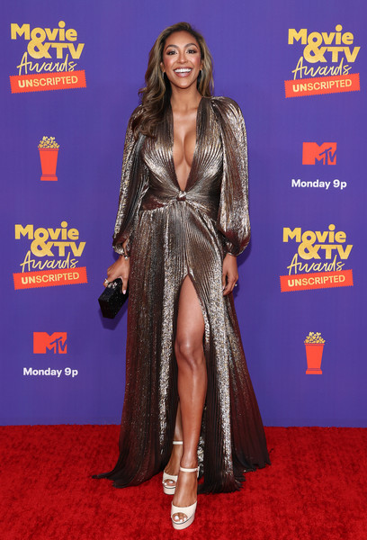 Tayshia Adams gleamed in a gold Oscar de la Renta gown with a plunging neckline and a high slit at the 2021 MTV Movie & TV Awards: UNSCRIPTED.