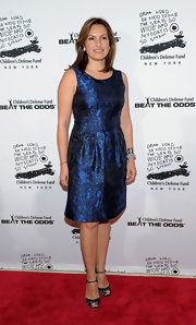 Mariska wears an iridescent print blue cocktail dress.