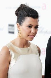 Kourtney Kardashian wore her hair pulled back into a casual loose bun at the Elton John Oscar viewing party.