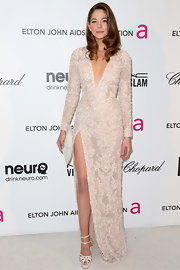 Analeigh Tipton attended Elton John's Oscars viewing party sporting a long-sleeve, fully-plunging neckline gown with a front slit.