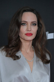 Angelina Jolie brightened up her beauty look with a swipe of red lipstick.