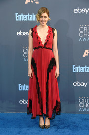 Greta Gerwig coordinated her dress with a pair of black lace pumps.