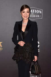 Michelle Yeoh paired a striped purse with a ruffled tuxedo for the 2018 Hollywood Film Awards.