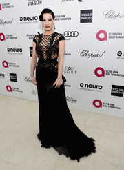 Dita Von Teese looked flawlessly chic, as always, in a black Zuhair Murad gown with a sheer lattice bodice during Elton John's Oscar-viewing party.