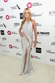 Heidi Klum put on a seductive display at Elton John's Oscar-viewing party in a glittery silver Atelier Versace gown with groin-and-leg-baring cutouts.