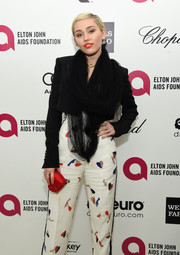 Miley Cyrus showed her unique style with this black mesh scarf by Schiaparelli Couture at the Elton John AIDS Foundation Oscar-viewing party.