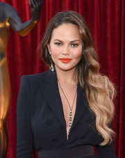 Chrissy Teigen brightened up her beauty look with a swipe of red-orange lipstick.