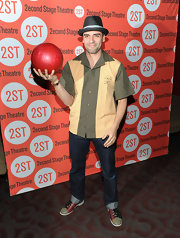 Oscar shows off his bowling finesse wearing a casual fedora and bowling shoes.