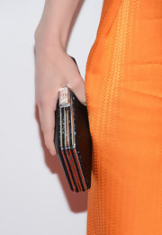 The actress paired her orange dress with a shiny black clutch.