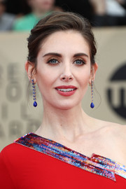 Alison Brie complemented her colorful dress with a pair of blue gemstone drop earrings by Irene Neuwirth.