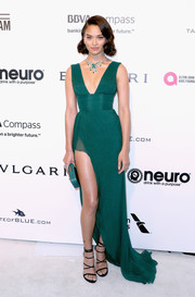Shanina Shaik was a stunner at the Elton John AIDS Foundation Oscar-viewing party in a cleavage-and-leg-flaunting emerald empire gown by Thai Nguyen Atelier.