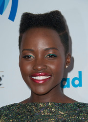 Lupita Nyong'o added more shimmer with some frosted pink lipstick.