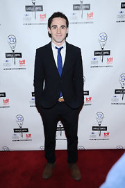Ari Brand chose a black suit, a blue tie, and old shoes for his Lucille Lortel Awards red carpet look.