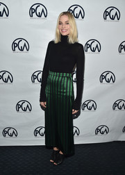 Margot Robbie dressed up her sweater with an emerald and black striped maxi skirt.