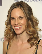 Actress Hilary Swank styled her honey-brown locks in soft spiral curls. A subtle side part finished her look look.