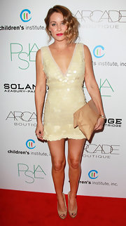 Lauren Conrad contrasted the dressy vibe of her shimmery sequined frock with a tan snakeskin envelope bag.