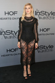Nicola Peltz complemented her frock with black peep-toe heels by Jimmy Choo.