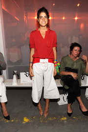 Leandra Medine attended the 3.1 Phillip Lim fashion show wearing a loose blouse in a bold red hue.