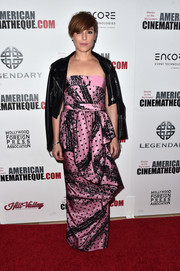 Noomi Rapace opted for a flirty pink and black strapless gown by Moschino, featuring a draped skirt and mixed prints, when she attended the American Cinematheque Awards.