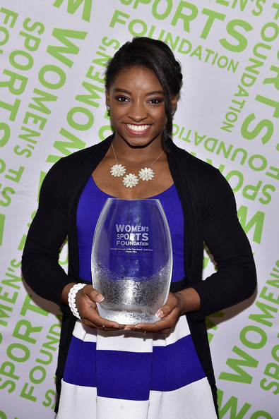 Simone Biles layered a black cardigan over a blue and white dress for the Salute to Women in Sports reception.