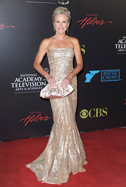 Beth showed off her gold metallic clutch while hitting the Daytime Emmy Awards red carpet.