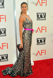 Gisele accessorized her glamorous ensemble with a metallic clutch.