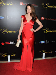Andie MacDowell walked the Gracie Awards red carpet wearing a lovely red Johanna Johnson gown featuring cap sleeves, a plunging neckline, and a front slit.