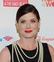 Debra Messing swept on a bold orange-red lipstick for the 3rd Annual Women in the World Summit.