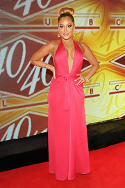 Adrienne Bailon chose a hot pink halter dress with a plunging neck and belted waist for her red carpet look.