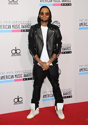 Chris Brown melted hearts in a black leather jacket as he posed for photographs at the American Music Awards.