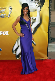 Shaun Robinson added shine to her glam purple gown with a silver hard case clutch.