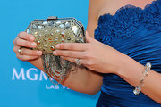 Katie held her buckled clutch high to show off the intricate detailing, while walking the orange carpet.