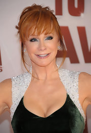 Reba McEntire wore her hair in a pretty updo with lash-grazing bangs at the 45th Annual CMA Awards.