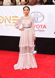 Logan Browning paired her dress with a spherical silver purse.