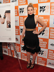 Elizabeth Olsen topped off her black and gold ensemble with a chic skull clasp clutch.