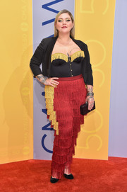 Elle King completed her eye-catching red carpet attire with a black cropped jacket and fringed pants.