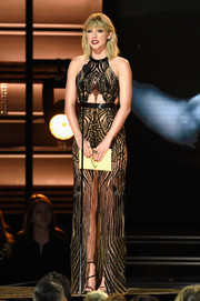 Taylor Swift showed her seductive side in a sheer striped cutout gown by Julien Macdonald at the CMA Awards.