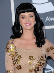 The always stylish Katy Perry shows off her offbeat style with these dangling skull earrings which add some funky edge to her feminine dress.