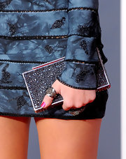 Miley adds this gemstone encrusted box clutch to her navy colored dress.