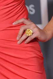 This gold flower ring really pops when paired with Olivia's coral one-shouldered dress.