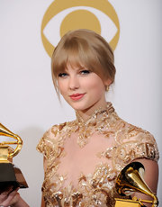 Taylor Swift attended the 54th Annual Grammy Awards wearing her hair in a classic bun with long wispy bangs.
