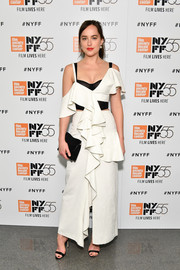 Dakota Johnson paired her dress with a black suede clutch by Proenza Schouler.