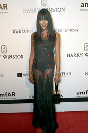 Naomi Campbell worked her signature sultry style at the amfAR Inspiration Gala Sao Paulo with this sheer, feathered Givenchy Couture gown studded all over with red sequins.