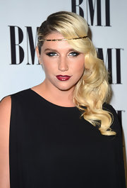 Kesha arrived at the BMI Pop Awards wearing her long hair in shiny side-swept curls with gold headband.