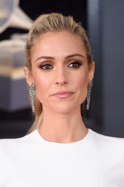 Kristin Cavallari accessorized with a pair of green gemstone chandelier earrings for a dash of color to her white outfit.