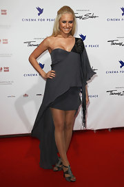 Alena wears a cutting edge slate gray gown with one sleeve and long fringe.