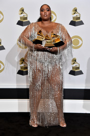 Lizzo showed off her Grammy awards wearing a sheer, fringed gown by Atelier Versace.