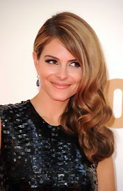 To duplicate Maria Menounos' sexy style, first set hair in hot rollers. Next, brush out curls with a natural bristle brush and mist with a workable hold hairspray. To finish the look, make a deep side part, put one side behind the ear and sweep the curls over to the side, letting them cascade over the shoulder.