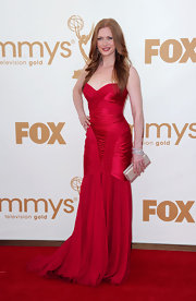 Mireille Enos was ravishing in red at the Emmys in a strapless raspberry silk gown. She finished off the look with loose tresses.
