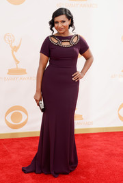 Mindy looked lovely as ever in a short sleeve plum silk gown with an embellished cut-out neckline.